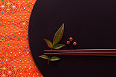 Pair of chopsticks with leaves and berries