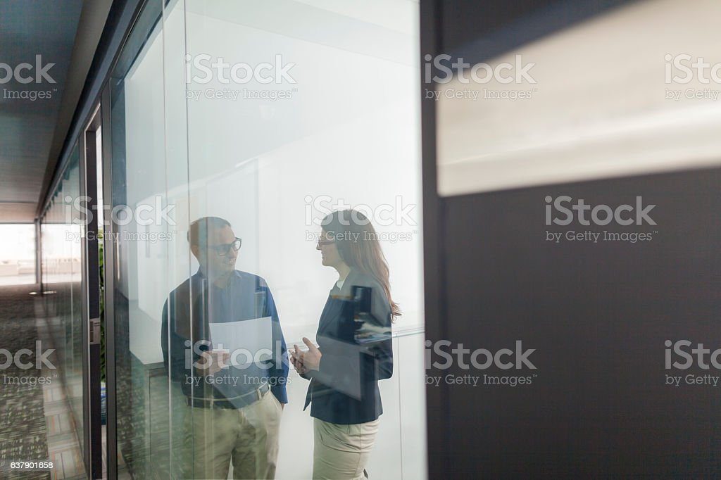Pair of colleagues talking together in office stock photo