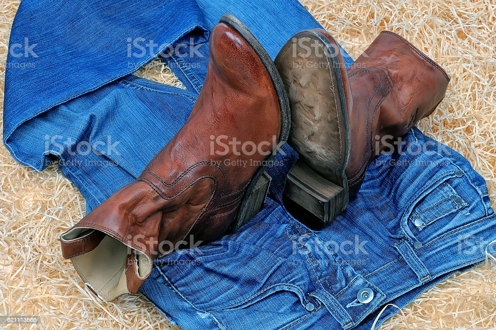 Pair of cowboy boots and blue jeans on straw stock photo