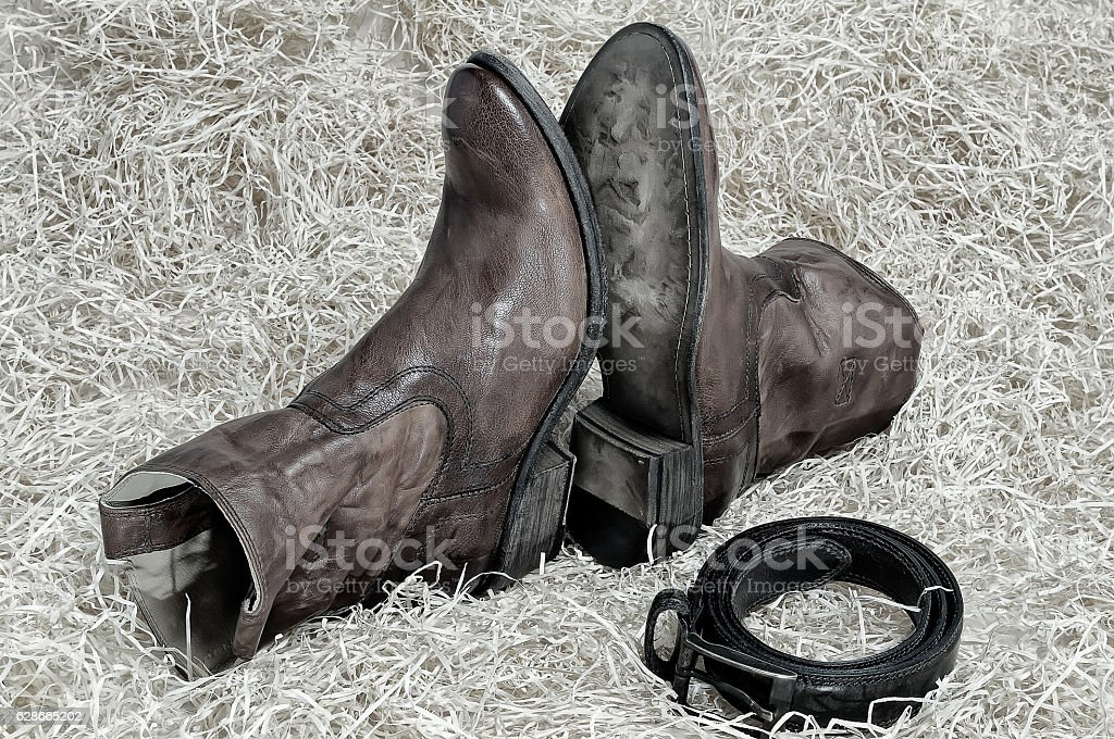 Pair of cowboy boots and leather belt on straw stock photo