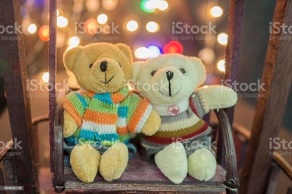 Pair of cute teddies sitting on wood swing bokeh background. stock photo