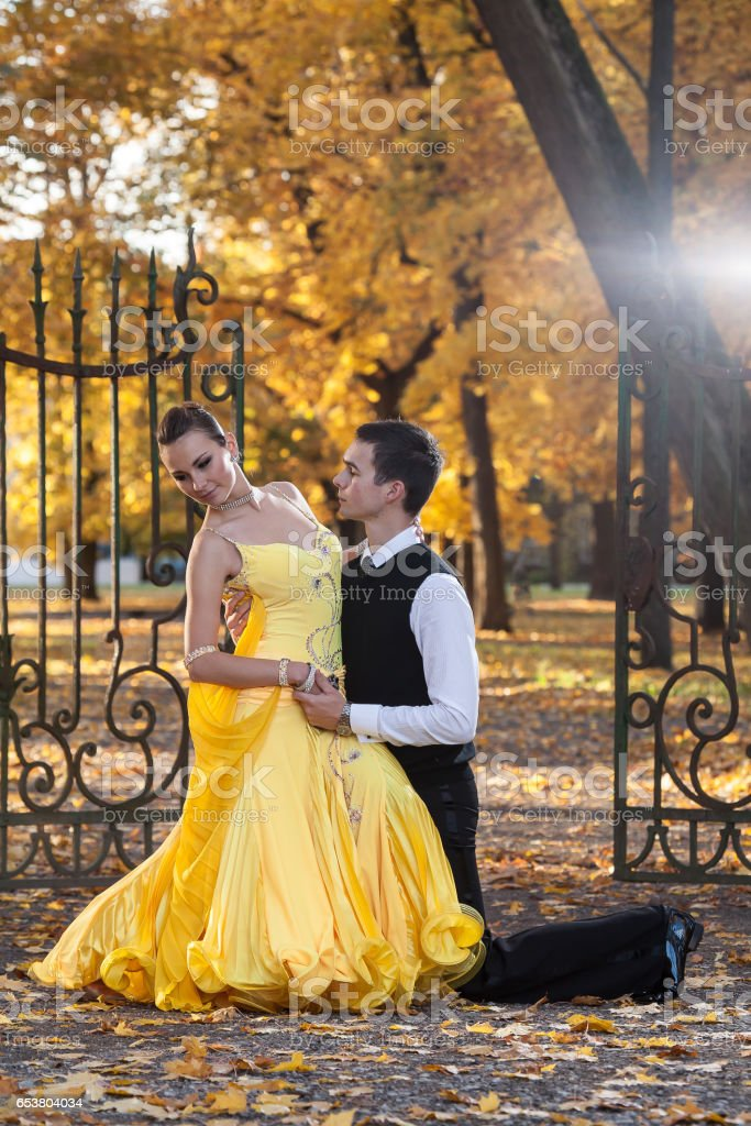 Pair of dancers dancing in the  palace garden. Man with suit and woman in a yellow long dress  in the middle of the park in autumn. Dry fallen colored leaves, trees gates in background stock photo