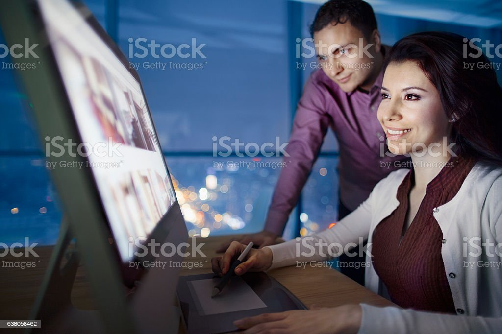Pair of designers reviewing images on computer at night stock photo