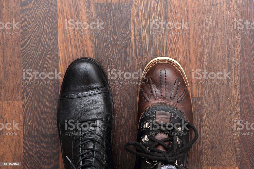 Pair of different mens leather boots on parquet stock photo