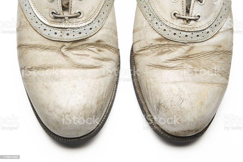 Pair of dirty golf shoes against white background stock photo