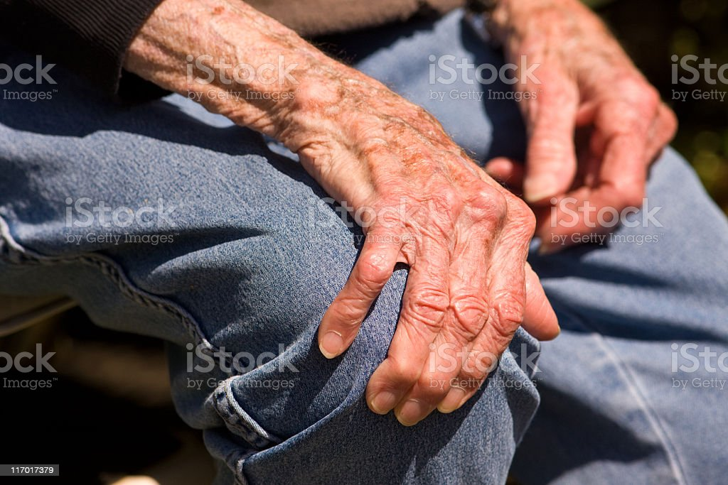 A pair of elderly hands grasping a denim clad knee stock photo
