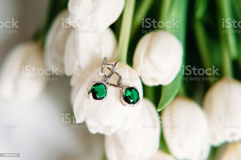 Pair of emerald earrings lying on flowers. White tulips. Jewelry stock photo