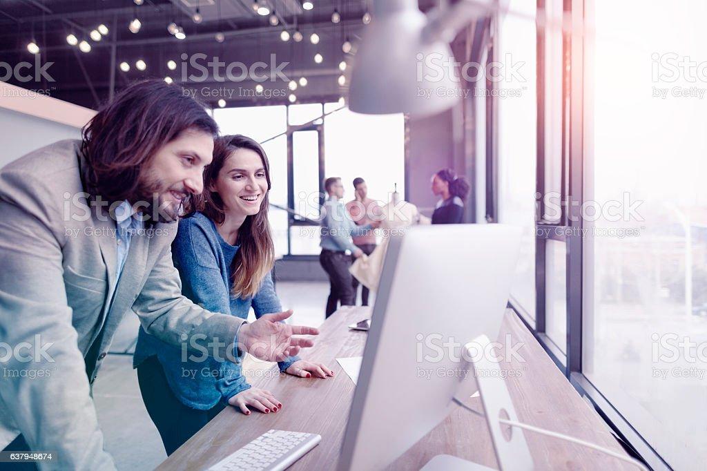 Pair of fashion designers discussing ideas in design studio environment stock photo