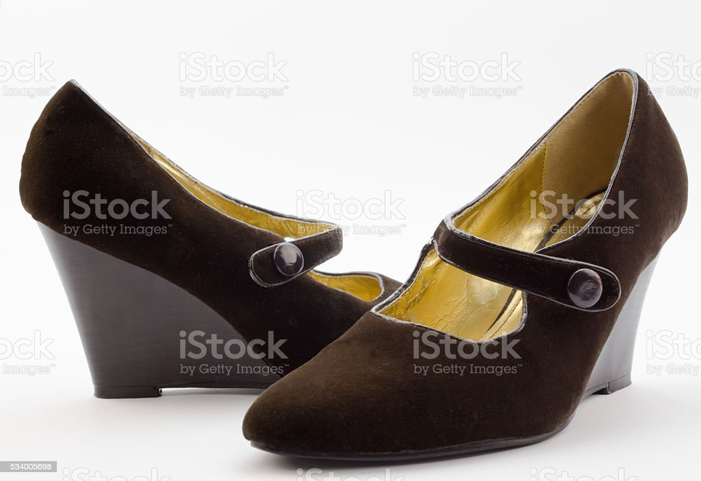 Pair of female brown velvet wedge heel shoes on white stock photo