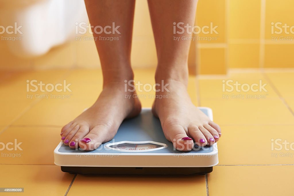 Pair of female feet on a bathroom scale stock photo
