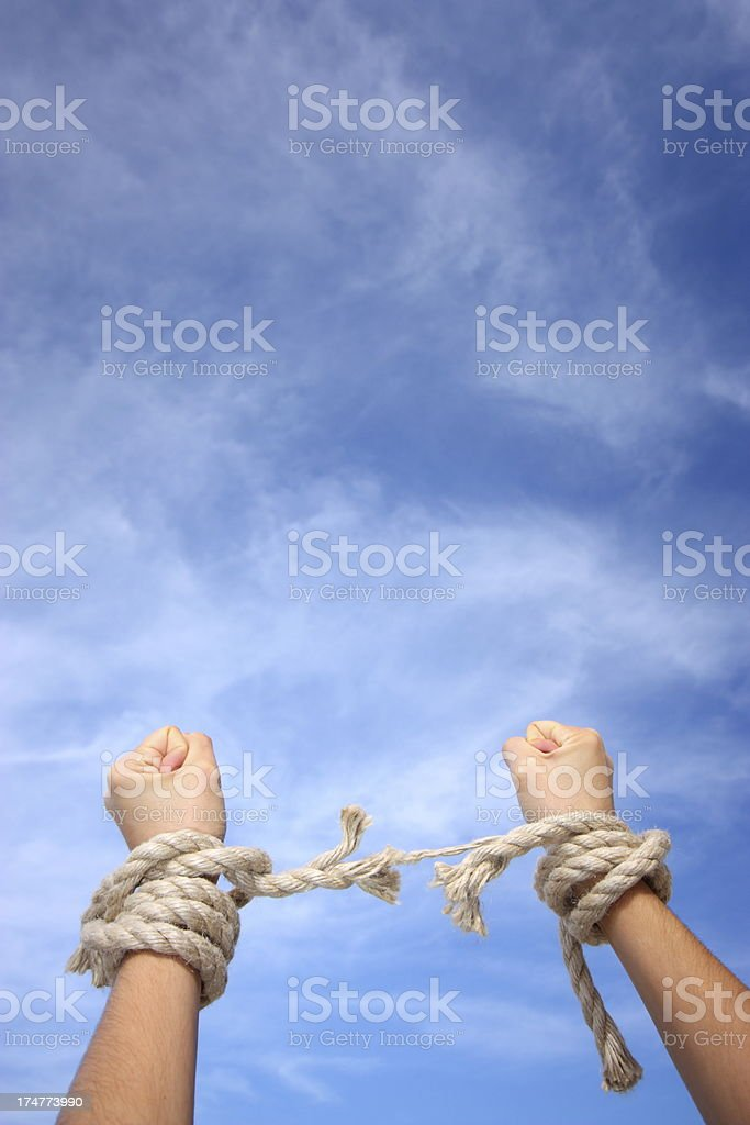 Pair of fists raised to the sky breaking free of ropes stock photo