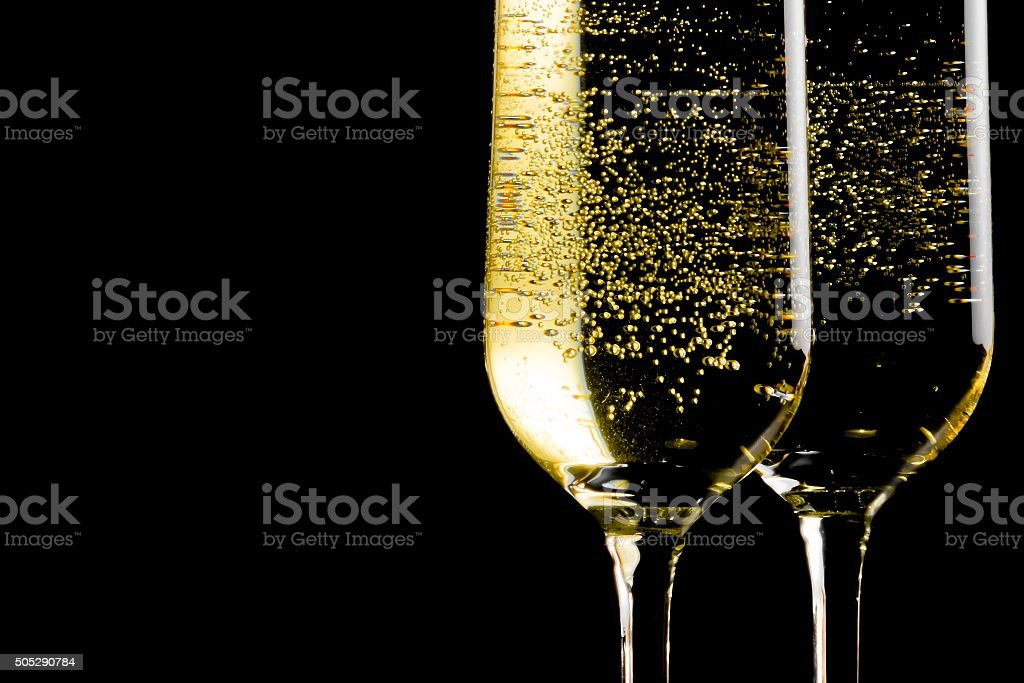 pair of flutes of champagne with golden bubbles stock photo
