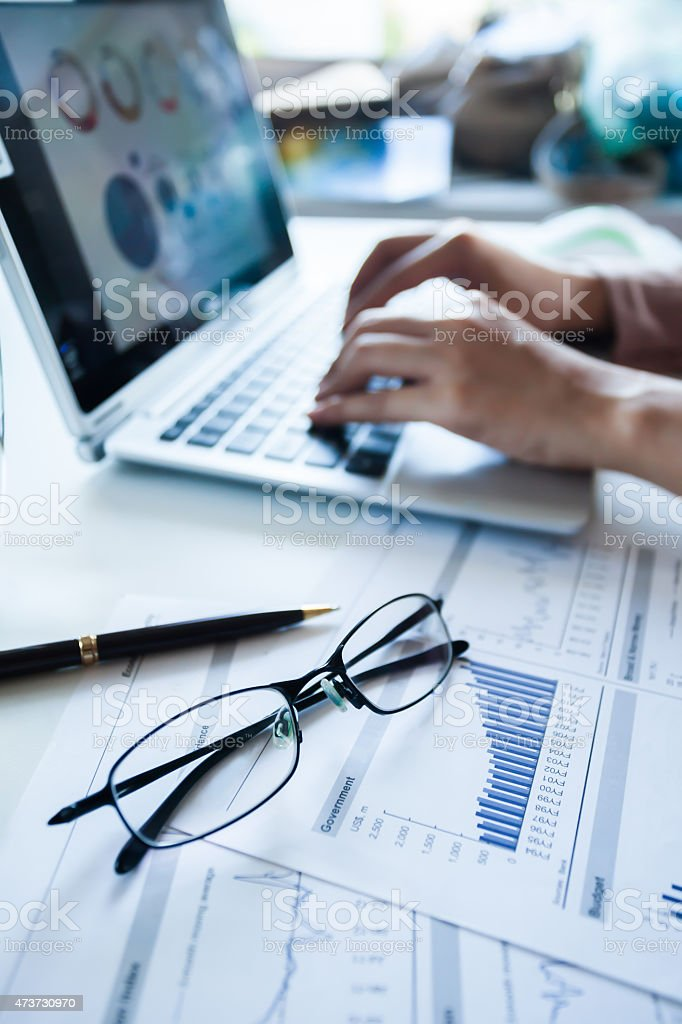 Pair of glasses laid over documents next to laptop in use stock photo