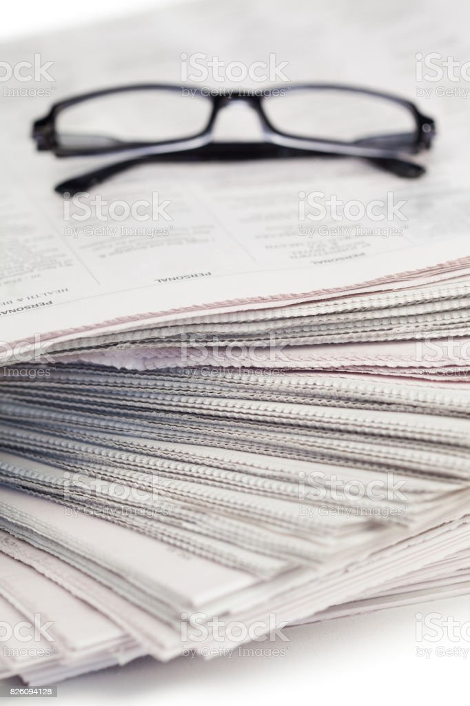 A pair of glasses on a pile of newspapers stock photo