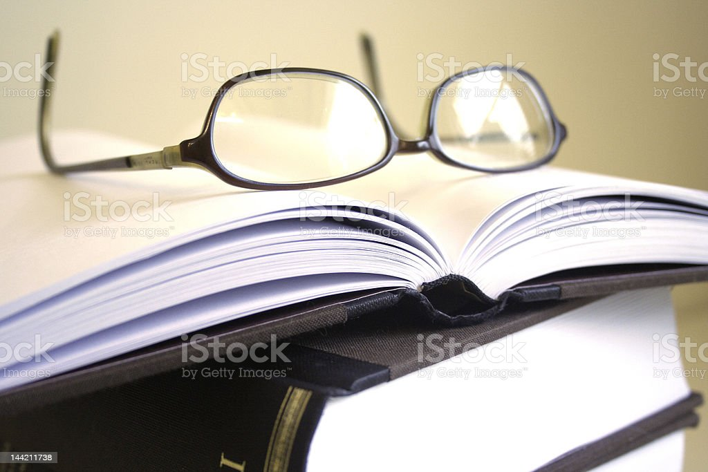 Pair of glasses resting on open book royalty-free stock photo