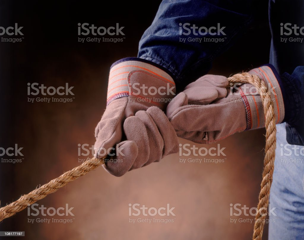 Pair of Gloved Hands Pulling on Rope royalty-free stock photo