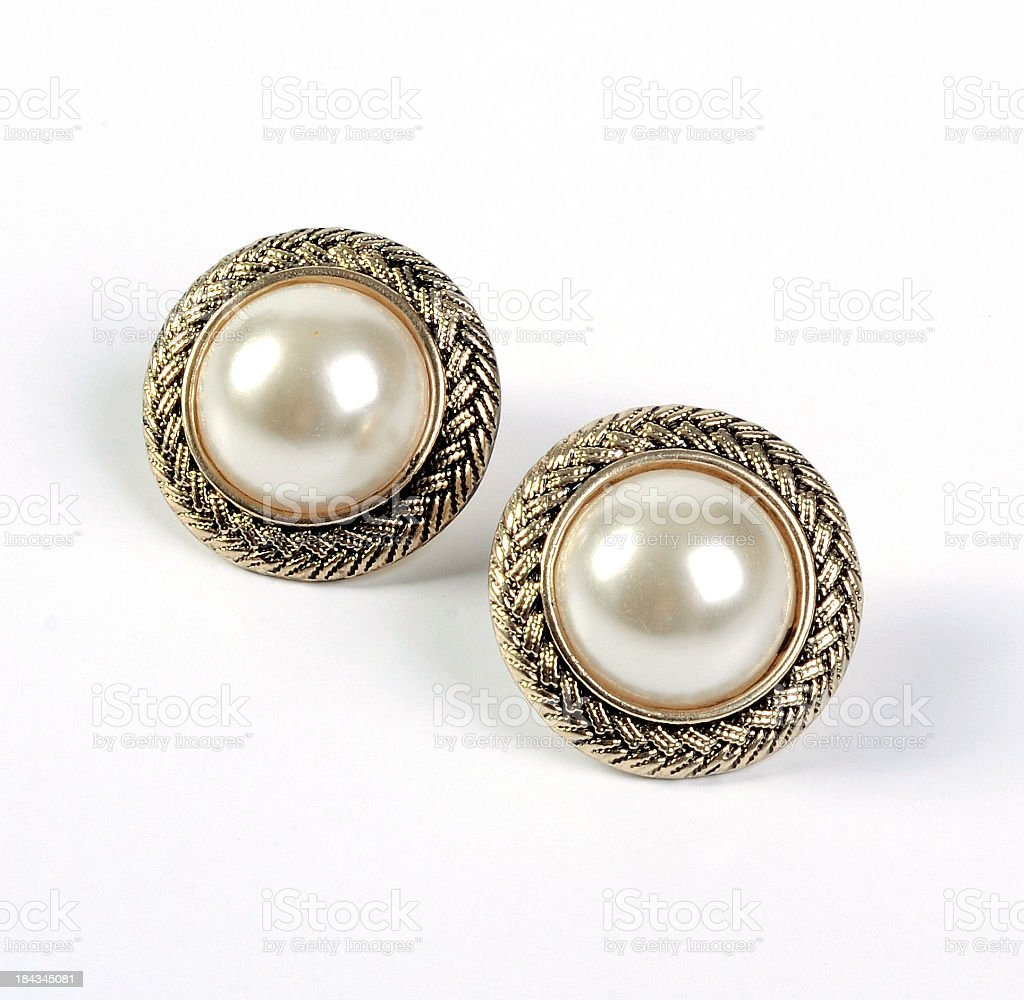 A pair of gold framed pearl stud earrings stock photo