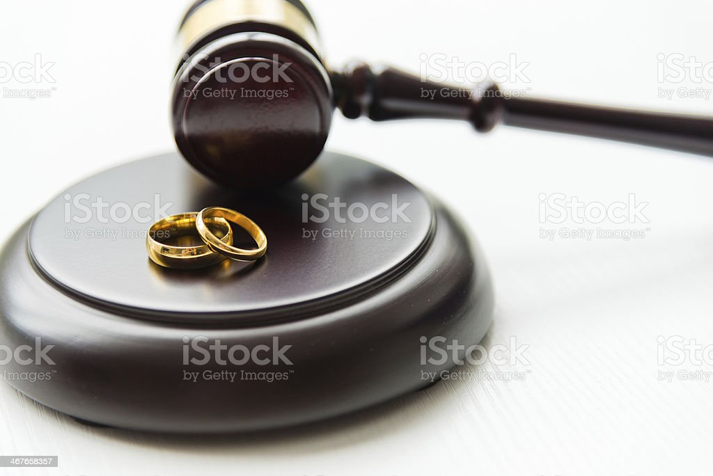Pair of gold rings next to wooden judge gavel stock photo