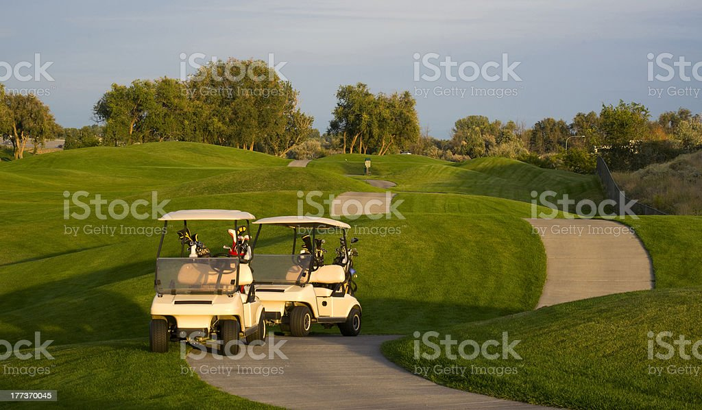 Pair of Golf Carts on the Green Course at Sunset stock photo