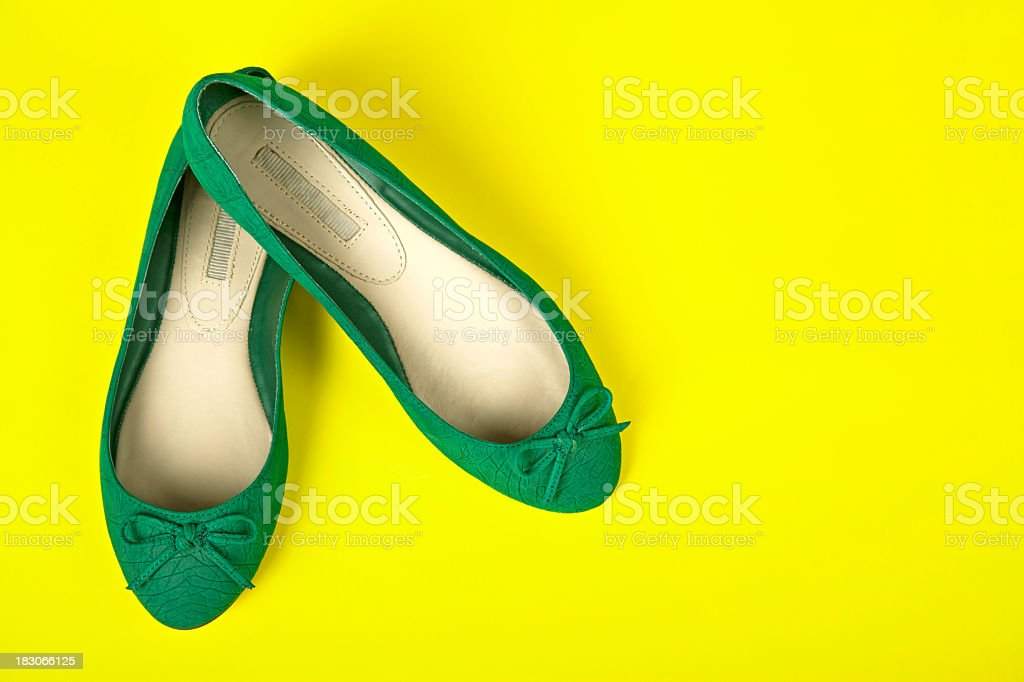 Pair of green shoes on a yellow background royalty-free stock photo