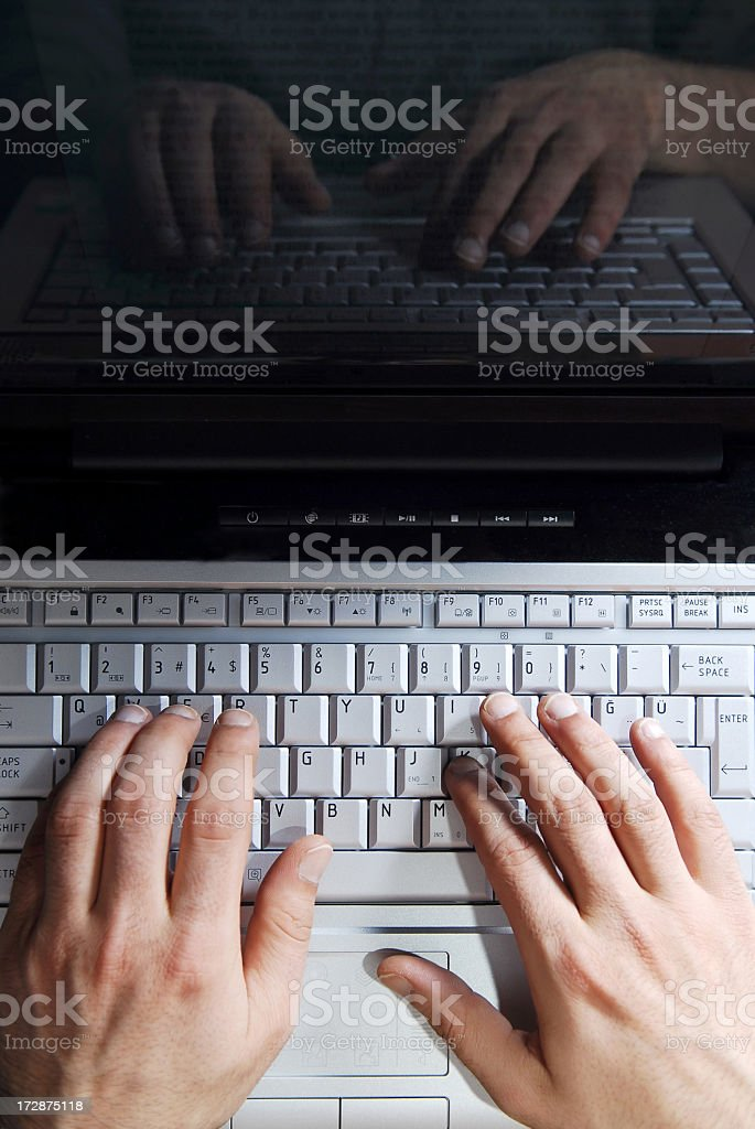 A pair of hands on a laptop keyboard stock photo
