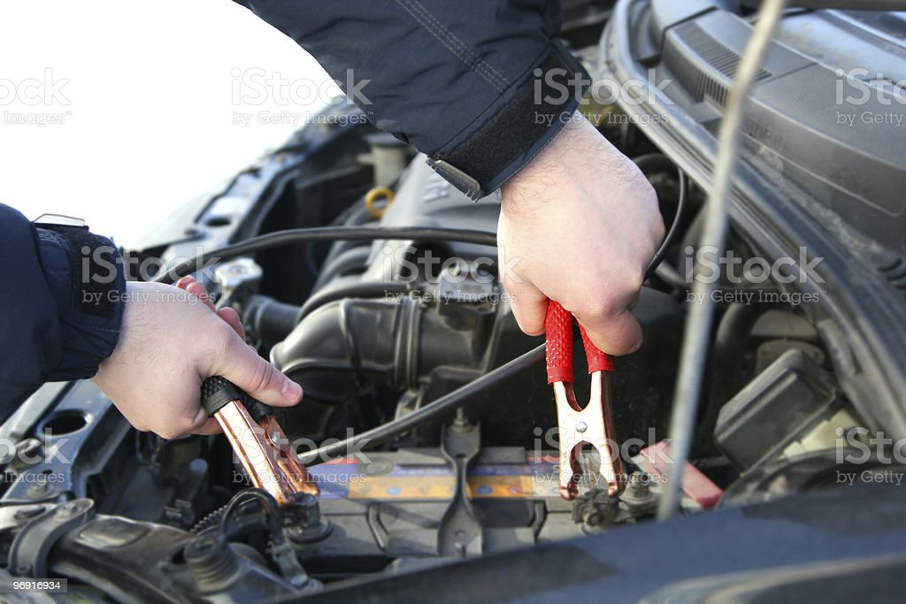 A pair of hands placing jumper cables on a battery stock photo