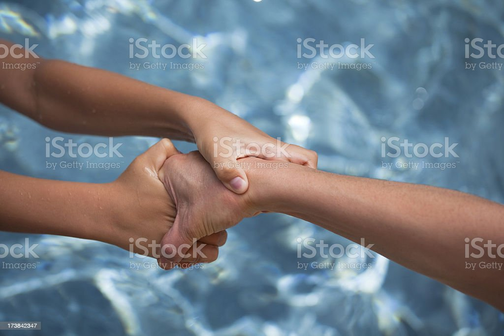 Pair of hands saving another human from water. royalty-free stock photo