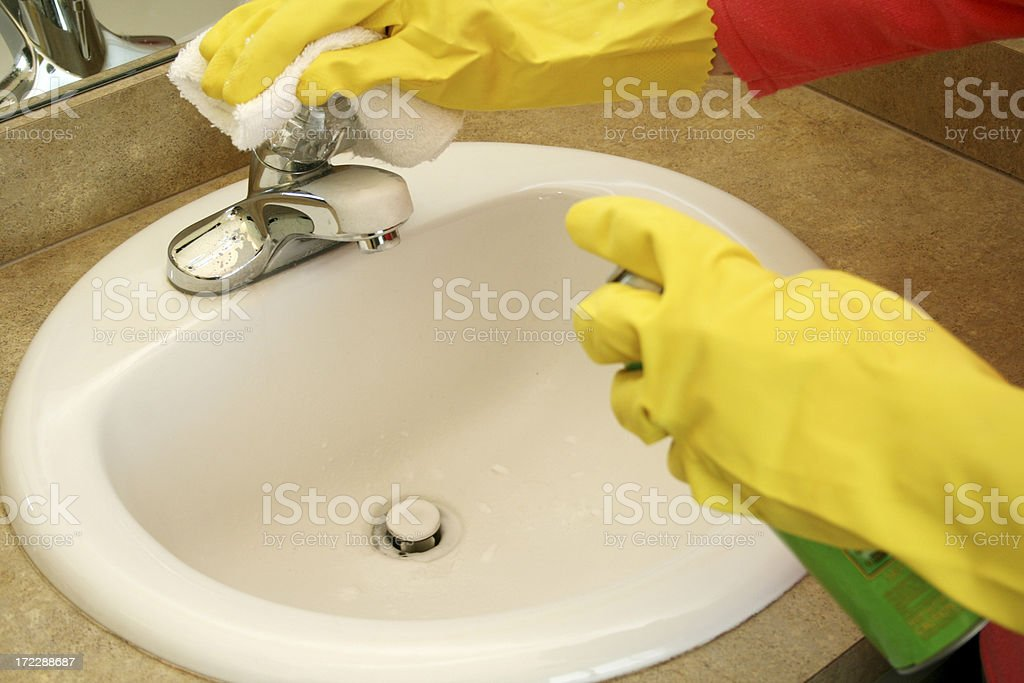 A pair of hands wearing rubber gloves cleaning a sink royalty-free stock photo