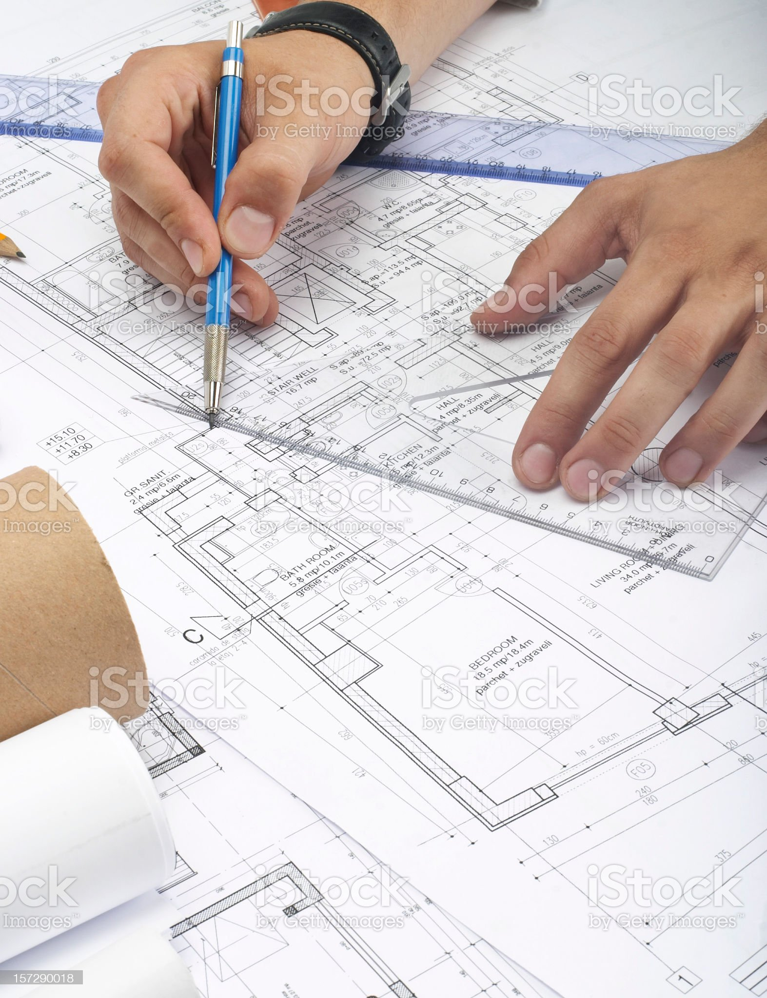 Pair of hands working on a blueprint using a ruler royalty-free stock photo