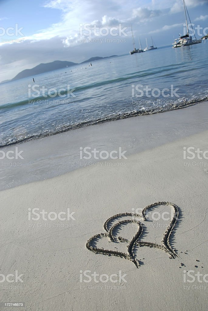 Pair of Interlocking Hearts Drawn on Tropical Beach royalty-free stock photo