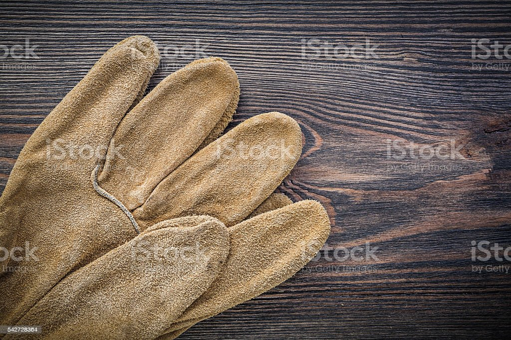 Pair of leather protective gloves on vintage wooden board agricu stock photo