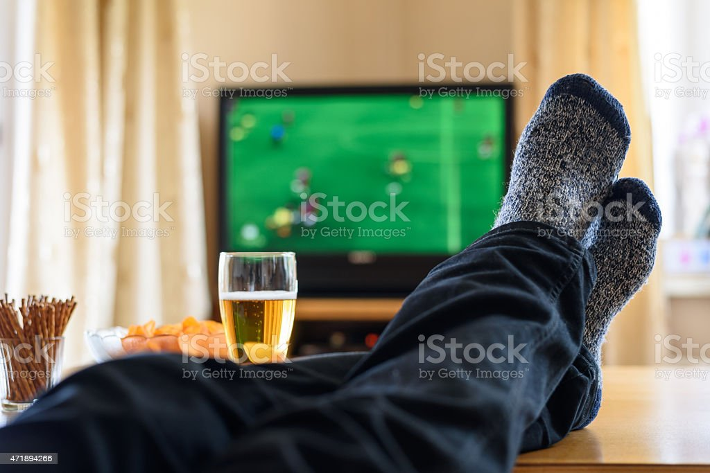 Pair of legs and feet resting on table next to snacks stock photo