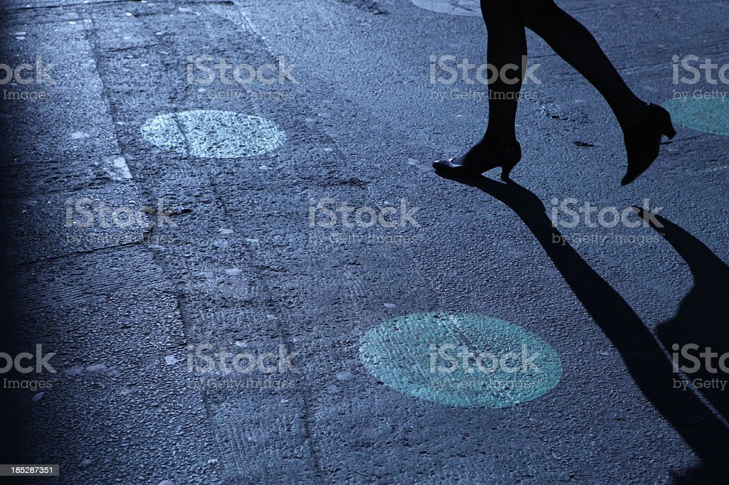 A pair of legs in heels walking on a street at night stock photo