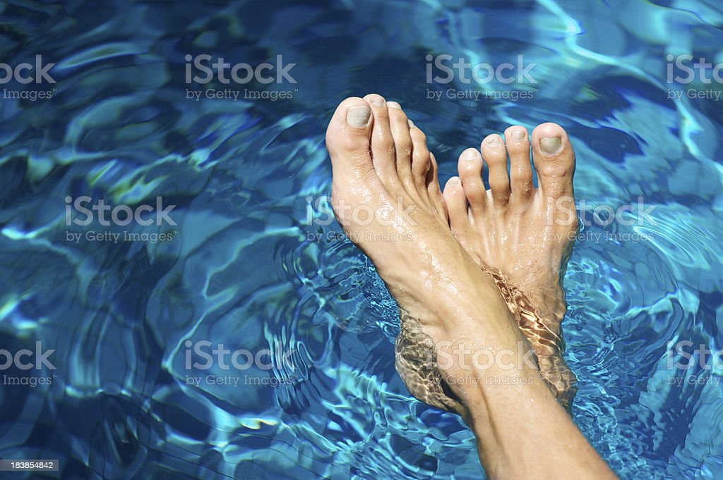 Pair of Male Feet Rest in Rippling Blue Water royalty-free stock photo