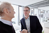 Pair of mature men talking together in design agency