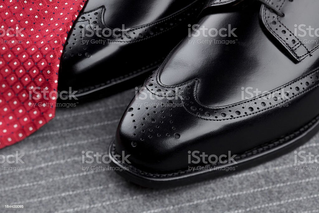 Pair of mens black shoes and red tie stock photo