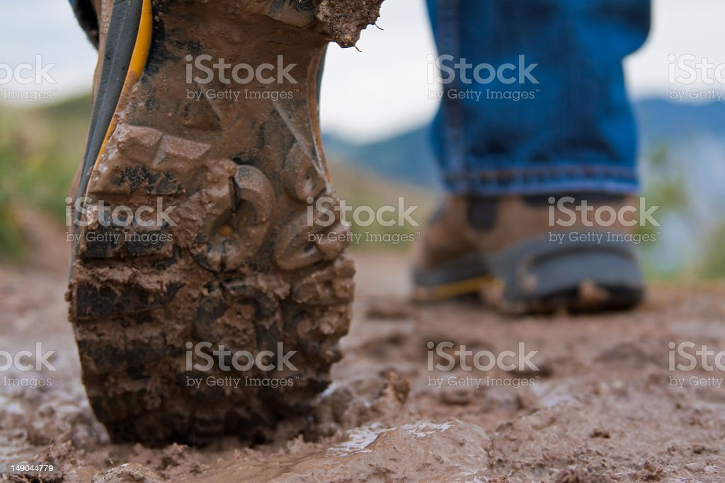 A pair of muddy hiking boots in the mud stock photo