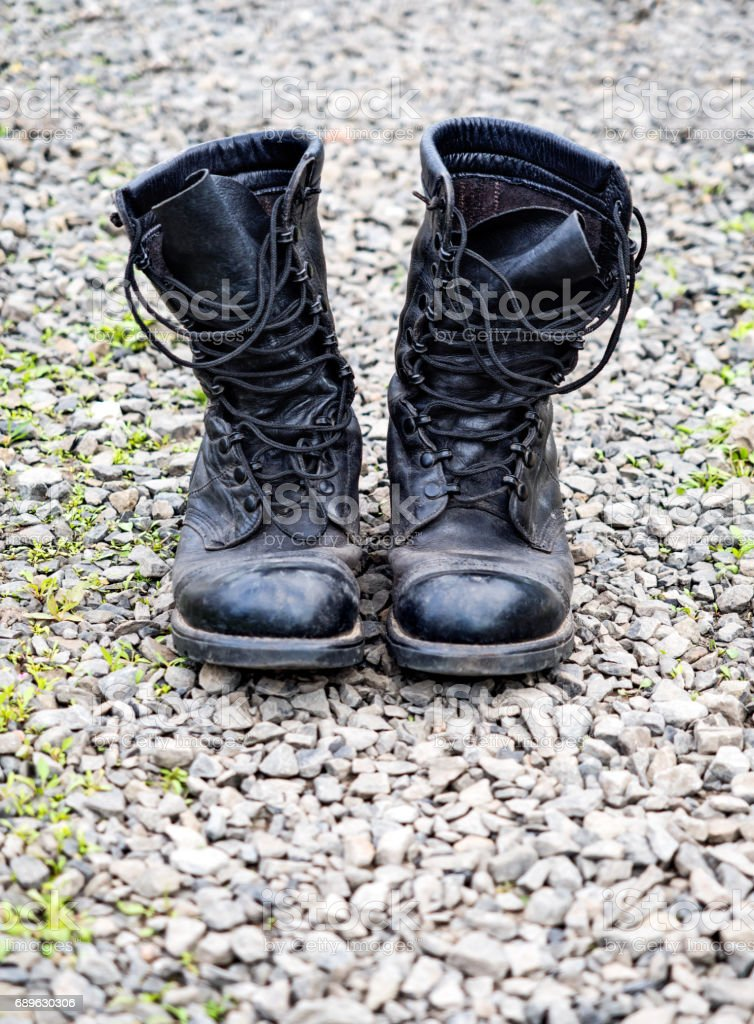 Pair of old army boots on stones surface stock photo