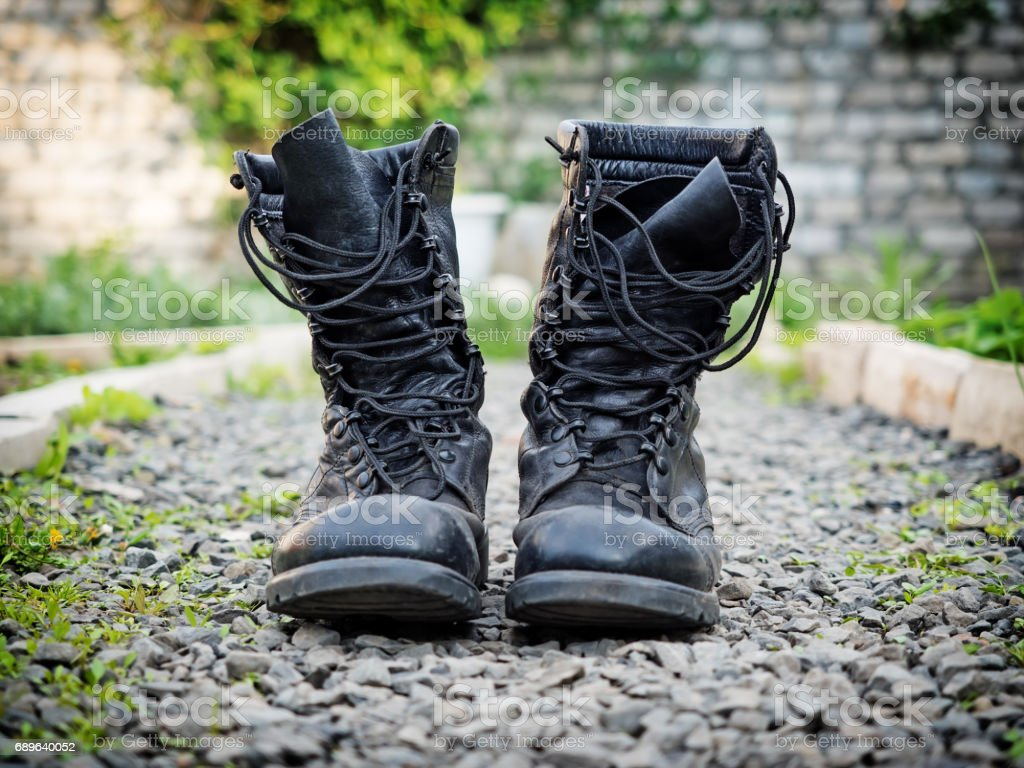 Pair of old army boots on stones surface, shallow depth of field stock photo