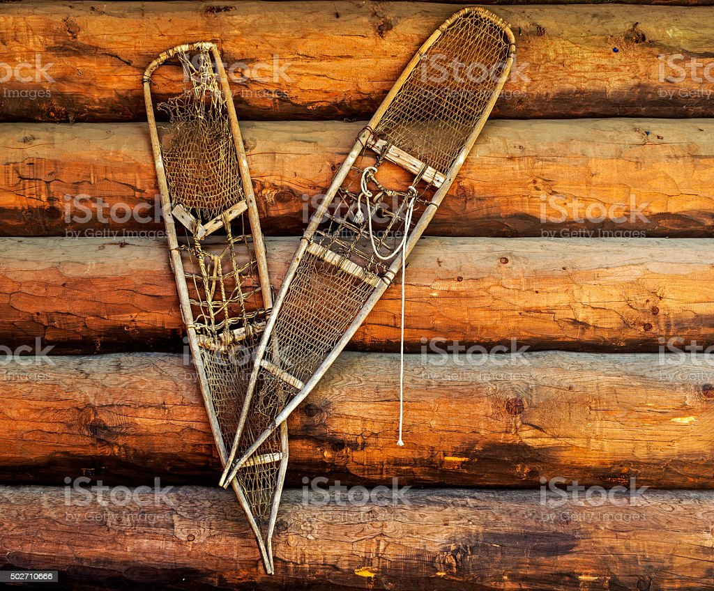 pair of old snow shoes on a wooden wall stock photo