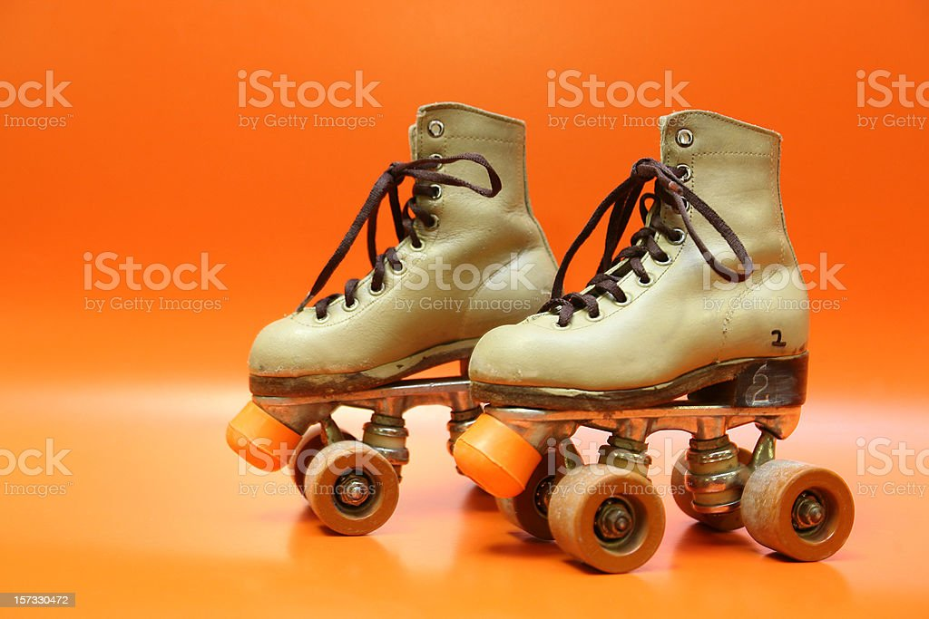 Pair of orange and brown four-wheel rollerblades with laces stock photo