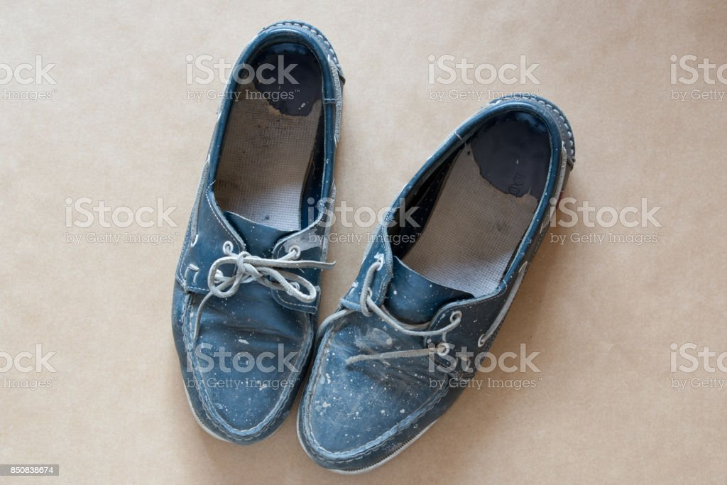 Pair of paint splattered men's blue shoes stock photo