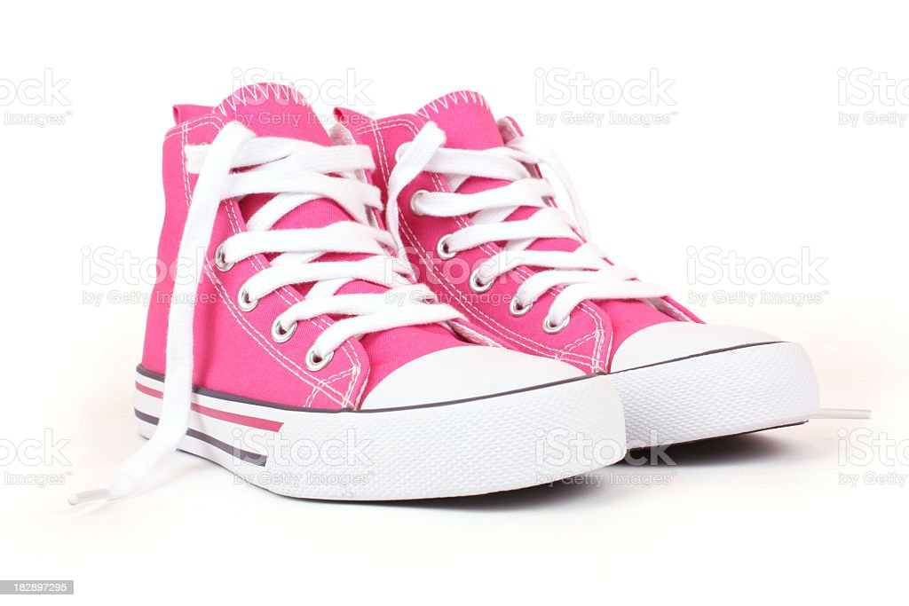 Pair of pink canvas sneakers with white laces stock photo