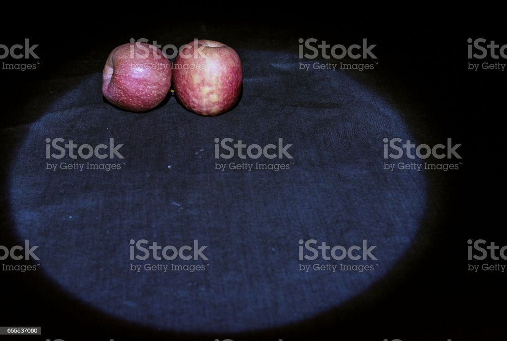 Pair of Pink Lady apples darkness illuminated by un LED light beam stock photo