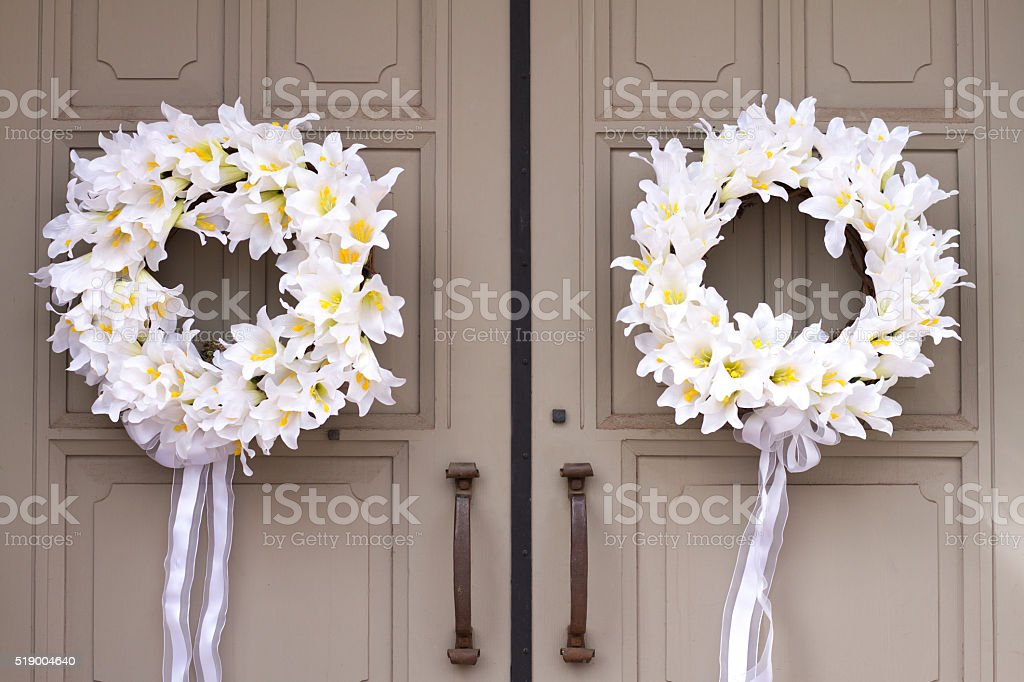 Pair of Pretty White Floral Wreaths on Tan Doors stock photo