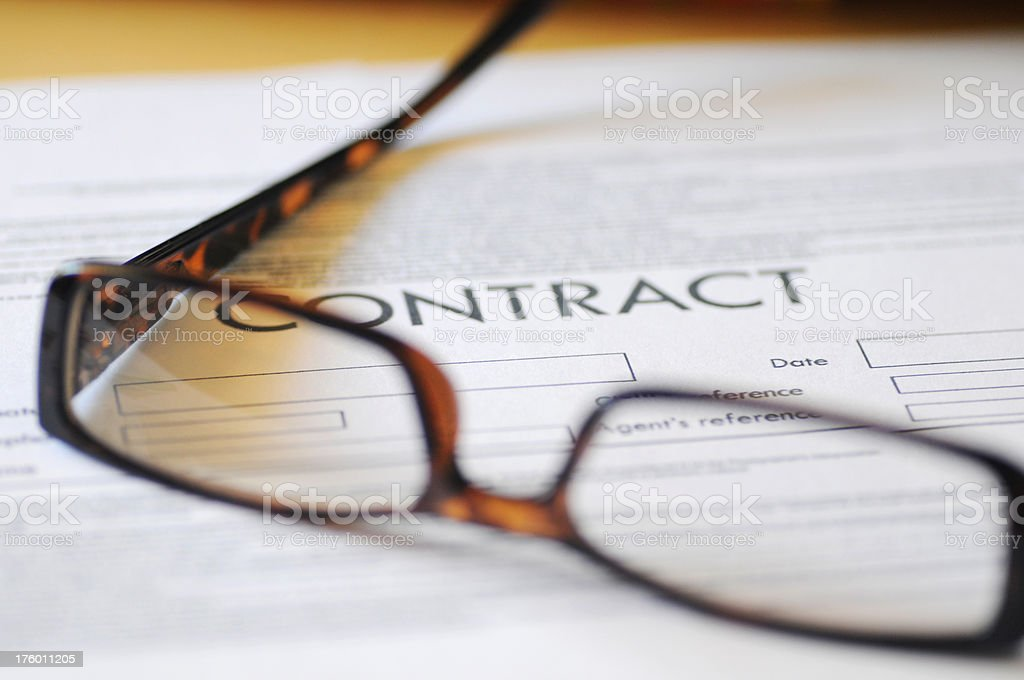 Pair of reading glasses resting on a contract royalty-free stock photo