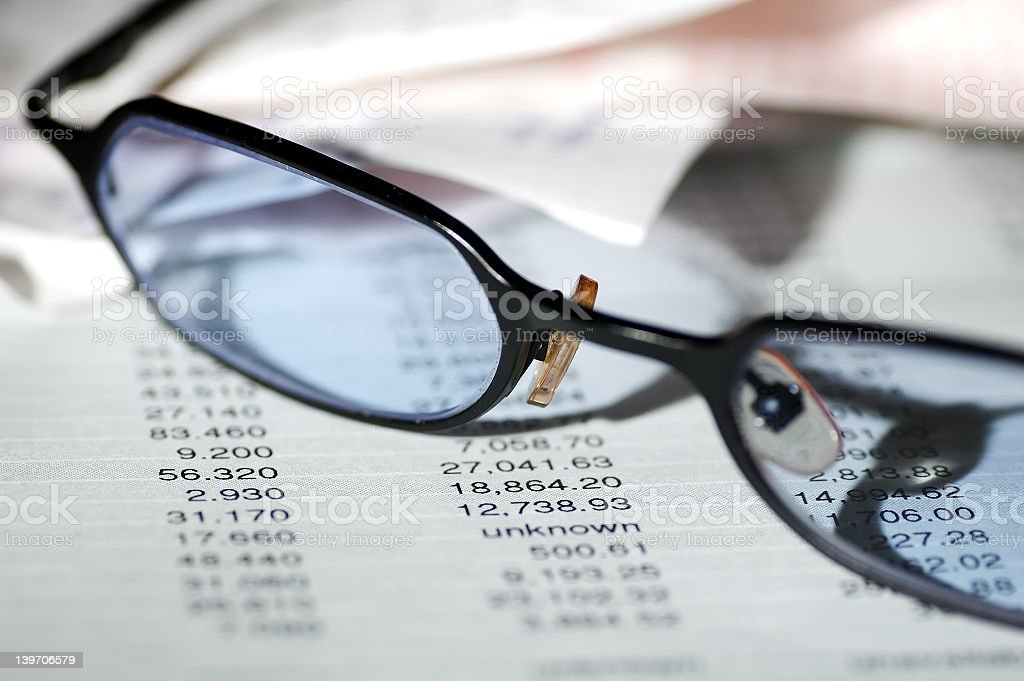 Pair of reading glasses resting on financial papers stock photo