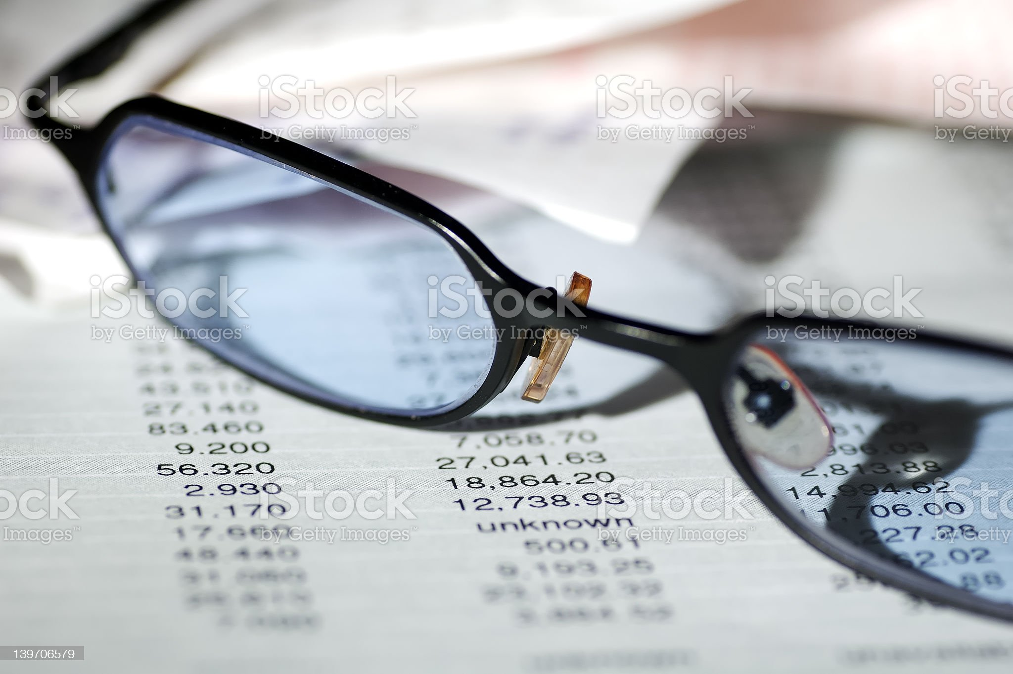 Pair of reading glasses resting on financial papers royalty-free stock photo
