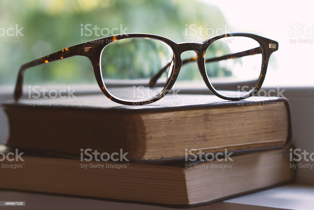 A pair of reading glasses set upon two reading books stock photo
