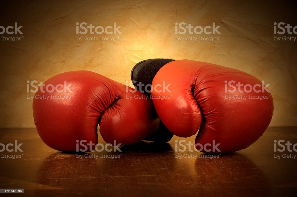 A pair of red boxing gloves on. Reflective brown surface royalty-free stock photo